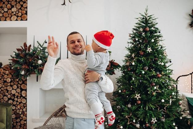 Foto da cintura para cima de um pai feliz acenando e segurando uma criança perto da árvore de natal