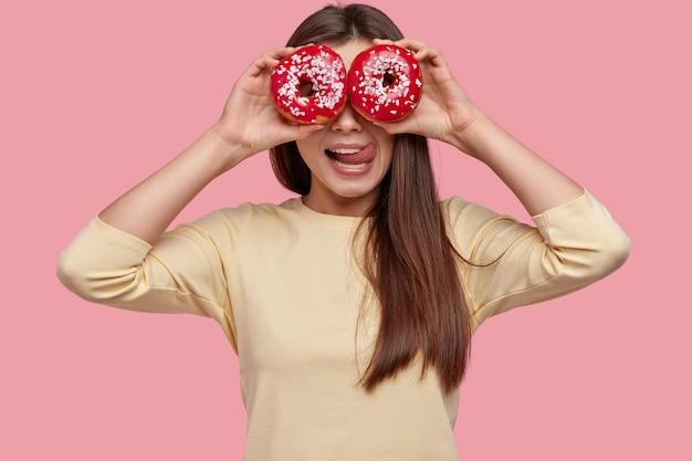 Foto da cintura para cima de uma bela jovem mostra a língua de um gosto agradável, cobre os olhos com donuts, se diverte dentro de casa, vestida com roupas amarelas