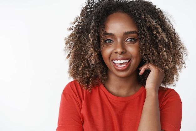 Foto da cintura para cima de uma esportista afro-americana bonita, saudável e feliz, com um lindo corte de cabelo encaracolado tocando o cabelo e sorrindo, encantada, parecendo energizada enquanto toma vitaminas sobre uma parede branca