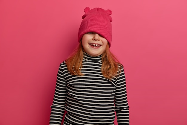 Foto da cintura para cima de uma garota adorável com um humor brincalhão, parece de cima do chapéu, brinca, usa blusão listrado, tem um sorriso largo, posa contra uma parede rosada, sendo desobediente ou travessa