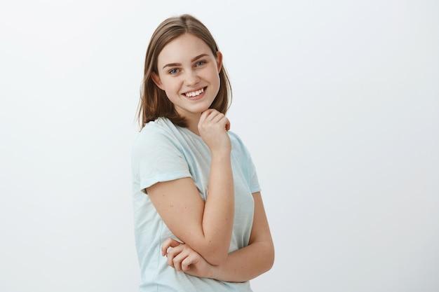 Foto da cintura para cima de uma garota feliz e alegre de aparência amigável com cabelo curto castanho em pé de perfil, segurando a mão na bochecha e virando-se com um largo sorriso feliz posando contra uma parede cinza