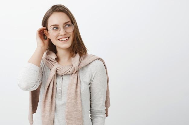 Foto da cintura para cima de uma garota feminina criativa e charmosa de óculos e pulôver tricotada no pescoço, colocando a mecha de cabelo atrás da orelha e olhando encantada e terna para a direita com um sorriso fofo