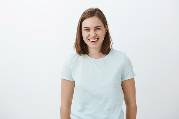 Foto da cintura para cima de uma garota morena comum, alegre, divertida e divertida, de boa aparência, em uma camiseta da moda, rindo alegremente e olhando para uma conversa divertida e divertida com amigos sobre a parede cinza