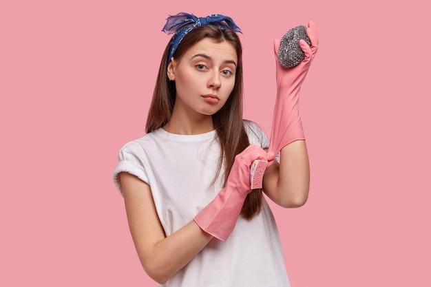 Foto da cintura para cima de uma jovem de aparência agradável usando luvas de proteção de borracha, usando duas esponjas, limpando hotel