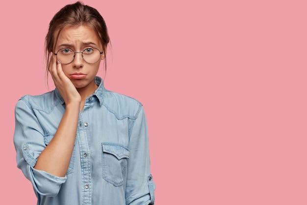 Foto da cintura para cima de uma linda mulher caucasiana deprimida com uma expressão facial miserável e uma camisa jeans elegante