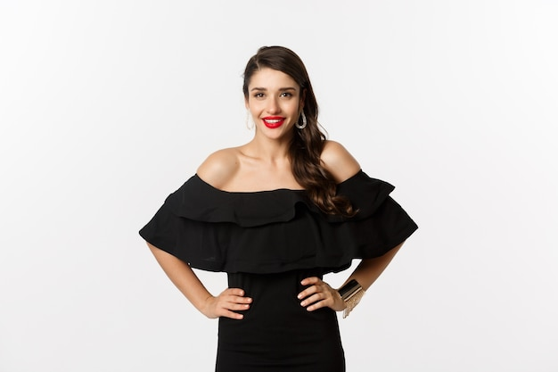 Foto da cintura para cima de uma linda mulher com batom vermelho, usando um vestido preto e sorrindo satisfeito, em pé sobre um fundo branco.