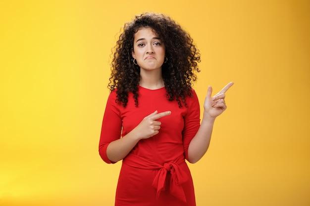 Foto da cintura para cima de uma menina chateada e descontente com o cabelo encaracolado caído apontando para o canto superior direito com um sorriso triste e desapontado, sentindo arrependimento, tristeza parada como uma perdedora sobre a parede amarela.