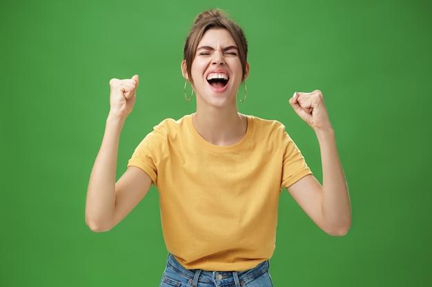 Foto da cintura para cima de uma mulher carismática energizada e animada em uma camiseta amarela, fechando os olhos e gritando de alegria e felicidade, levantando as mãos em comemoração às notícias de sucesso sobre a parede verde.