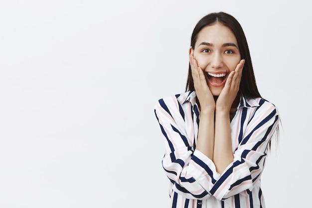 Foto da cintura para cima de uma mulher mongol atraente feliz emocionada com longos cabelos escuros naturais, sorrindo amplamente, segurando as palmas das mãos nas bochechas, ficando maravilhada e divertida com notícias impressionantes sobre a parede cinza