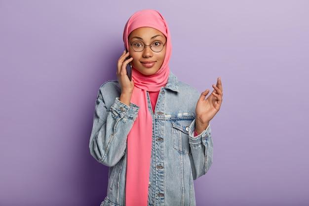 Foto da cintura para cima de uma mulher muçulmana que gosta de conversar no smartphone, sendo usuária de um dispositivo moderno, usa hijab rosa e jaqueta jeans, usa conexão pública com a internet, isolada na parede roxa