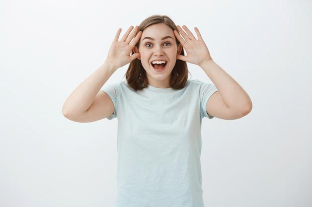 Foto da cintura para cima de uma mulher surpresa e satisfeita que não consegue acreditar que ela ganhou uma viagem participando da competição segurando as palmas das mãos perto do rosto sorrindo amplamente e animada olhando com olhar sonhador e encantado