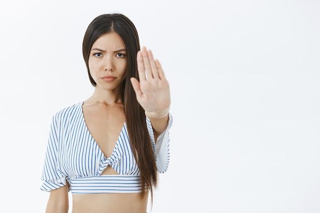 Foto da cintura para cima de uma namorada insatisfeita de aparência séria puxando o braço em direção à câmera e fazendo gestos suficientes