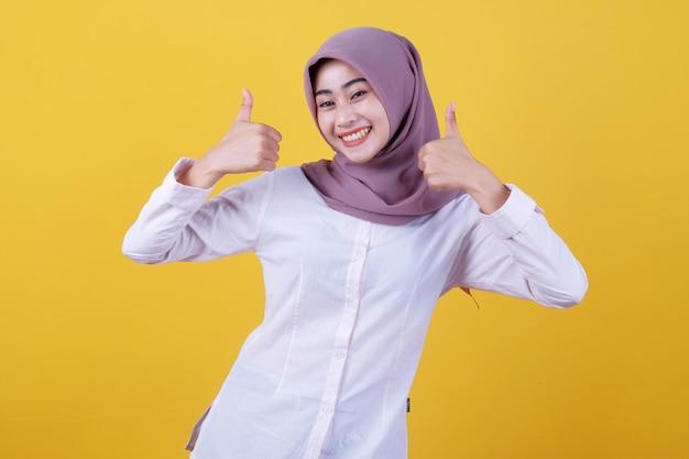 Foto da cintura para cima de uma senhora atraente que aceita o plano de um amigo, dá uma opinião positiva, mantém o polegar para cima, olha feliz