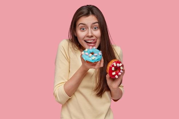 Foto da cintura para cima de uma senhora caucasiana feliz lambendo os lábios com a língua, segurando deliciosos donuts, não mantém a dieta