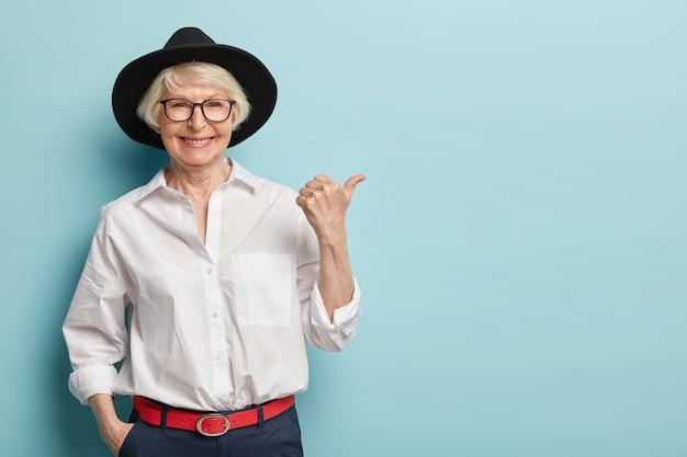 Foto da cintura para cima de uma senhora idosa de aparência amigável em um capacete estiloso, camisa branca elegante e calças formais, segura a mão no bolso, aponta o polegar para longe, tem um sorriso feliz, anuncia algo legal