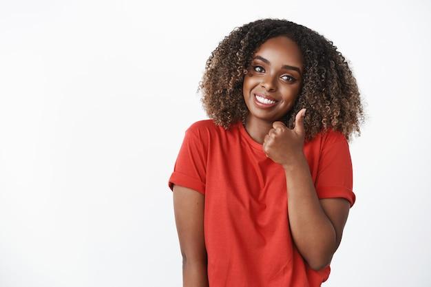 Foto da cintura para cima de uma simpática amiga afro-americana mostrando o polegar para cima e inclinando a cabeça em aprovação e sorrindo amplamente para animar a amiga e incentivar esforços excelentes sobre a parede branca