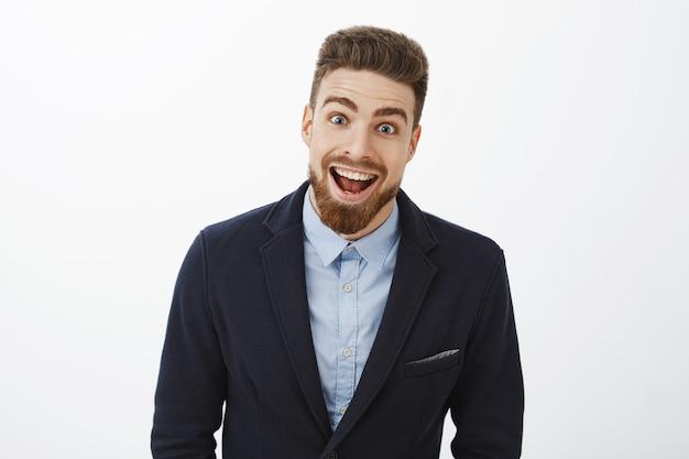 Foto da cintura para cima do entusiasmado, encantado e surpreso, jovem solteirão rico carismático em um terno estiloso com barba e olhos azuis sorrindo de espanto e alegria olhando impressionado