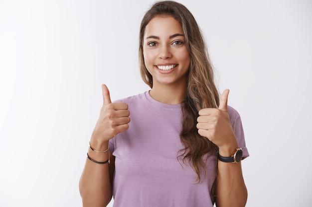 Foto da cintura para cima energizada jovem charmosa e extrovertida mulher moderna mostrando os polegares para cima sorrindo, satisfeita, aprovando, gostando de um produto legal, recomendando, torcendo e torcendo pelo namorado, parede branca de pé