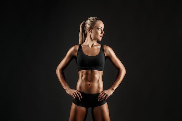 Foto da desportiva menina loira feminina mostrando volta seu corpo perfeito em preto