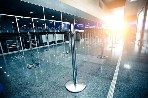 Foto da fila de check-in do aeroporto vazia iluminada por um raio de sol