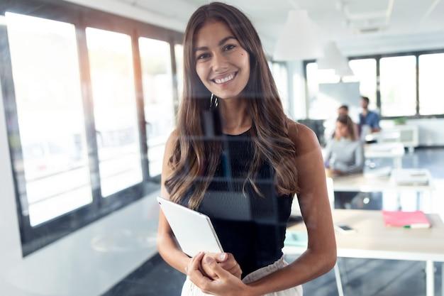 Foto da jovem empresária sorridente, olhando para a câmera em pé e segurando seu tablet digital no escritório moderno de inicialização.