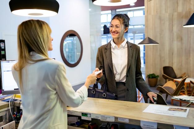 Foto da linda empresária leva cartão-chave do quarto e fazendo o check-in na recepção do hotel.