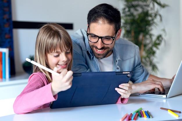 Foto da linda garotinha mostrando para o pai a foto que ela acabou de desenhar no tablet digital em casa.