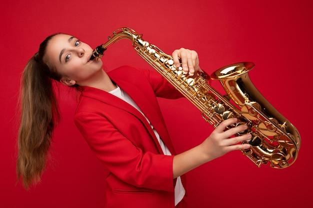 Foto da linda jovem morena positiva feliz vestindo uma elegante jaqueta vermelha isolada sobre a parede de fundo vermelho tocando saxofone, olhando para a câmera