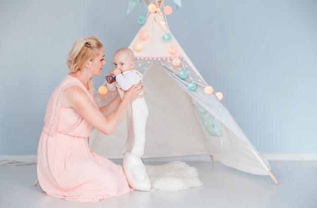 Foto da mãe alimentando o filho com uma garrafa em uma sala perto de uma tenda infantil