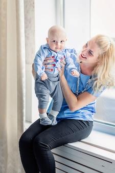 Foto da mãe com o filho pequeno sentado no parapeito da janela