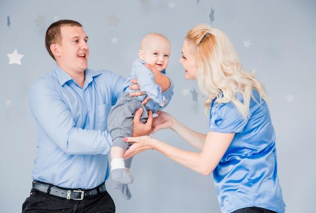 Foto da mãe e do pai brincando com o bebê vomitando