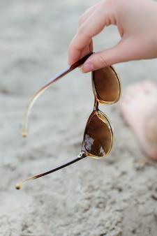 Foto da mão de uma mulher segurando óculos de sol contra a areia