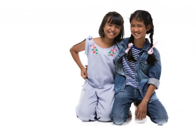 Foto da menina de dois asiáticos que olha a câmera com face do sorriso.