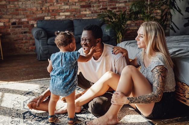 Foto da menina se divertindo com o pai e a mãe no quarto. família multiétnica feliz em casa.