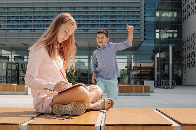 Foto da menina trabalhando no caderno com lápis, sentado no banco no pátio da escola. ambiente educacional informal, menino está correndo em direção a ela no fundo do prédio da escola
