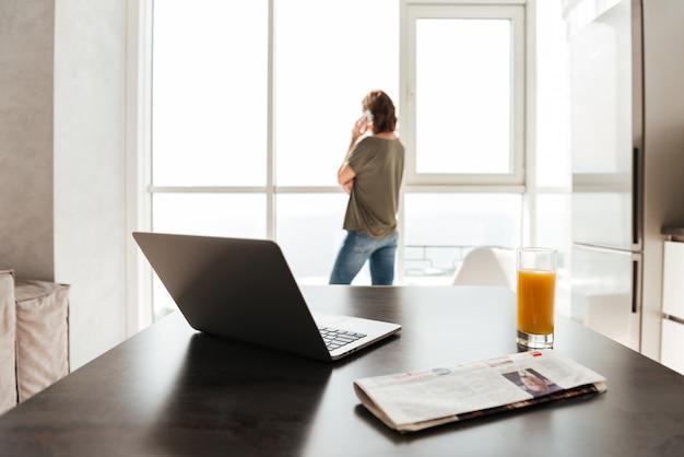 Foto da mesa com o computador portátil, suco, jornal e mulher perto da janela