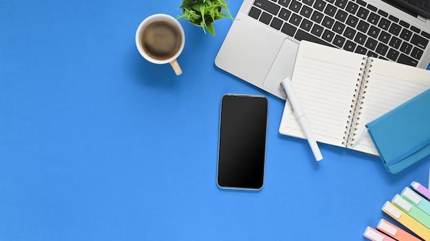 Foto da mesa de trabalho azul com o equipamento de escritório que põe sobre ele.