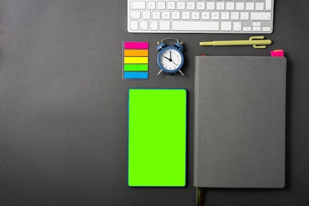 Foto da mesa de trabalho com simulação, tela verde no tablet, agenda, laptop e adesivos com despertador