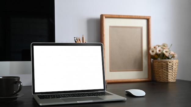Foto da mesa de trabalho preta junto com o laptop branco do computador da tela em branco, livros, caderno, suporte do lápis, moldura para retrato, planta em pasta que une nela com a parede do cimento branco.