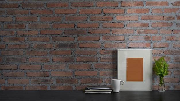 Foto da mesa de trabalho preta junto com o livro, o caderno, a moldura para retrato, a planta em vaso e o copo de café que montam nela com a parede de tijolo. conceito de espaço de trabalho ordenado.