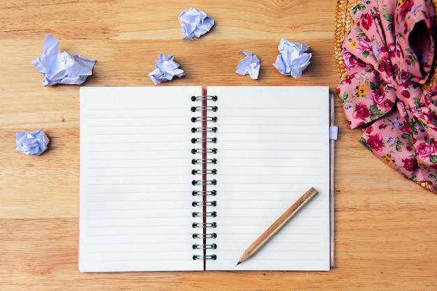 Foto da mesa, um caderno aberto com um lápis e um chapéu colocado ao lado do piso de madeira