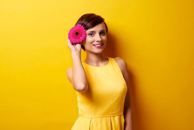 Foto da modelo segurando uma flor perto da orelha