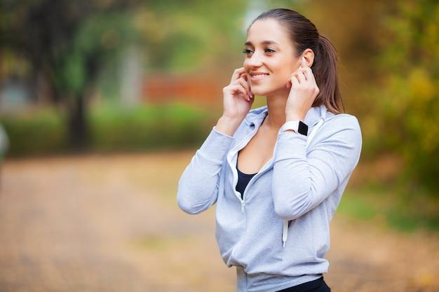 Foto da mulher alegre fitness 30 anos no sportswear tocando bluetooth earpod e segurando o telefone móvel, enquanto descansava no parque verde