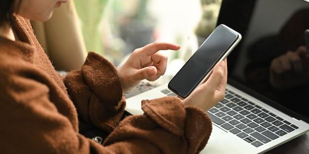 Foto da mulher bonita que relaxa em suas férias usando um smartphone preto da tela em branco ao sentar-se na frente seu laptop preto do computador da tela em branco no sofá de couro na sala de estar moderna.