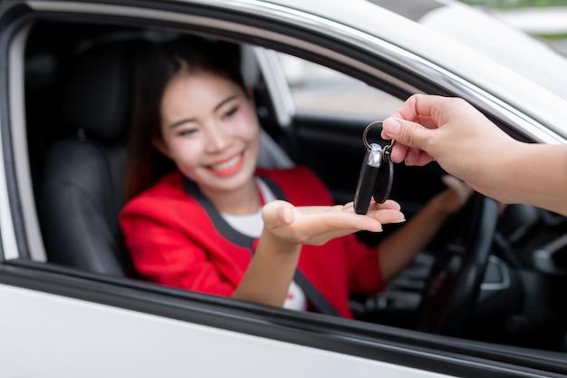 Foto da mulher nova feliz da raça misturada que mostra a chave a seu carro novo. conceito para o aluguer de automóveis.