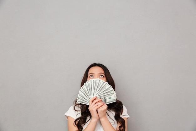 Foto da mulher rica asiática 20s, cobrindo o rosto com ventilador de notas de dólar de dinheiro e olhando para cima, isolado sobre a parede cinza