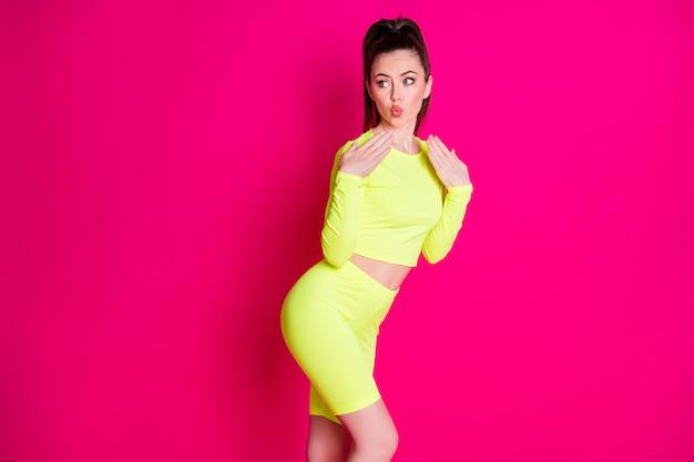 Foto da namorada adorável vestida com roupa amarela parecendo um espaço vazio com lábios fazendo beicinho mãos braços isolados de fundo cor de rosa