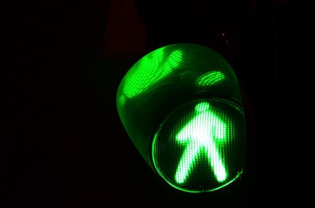 Foto da noite de um semáforo para pedestres, que acende em verde