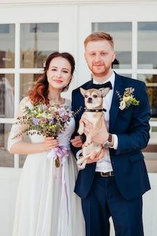 Foto da noiva e do noivo no dia do casamento com seu cachorrinho