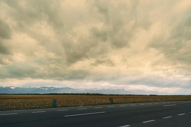 Foto da paisagem com uma parte da estrada, trigo e montanhas em um dia nublado.